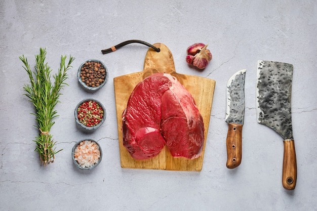 Overhead view of raw fresh deer boneless ham  with spice and herb over concrete background