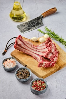 Overhead view of raw fresh doe ribs with spice and herb over concrete background
