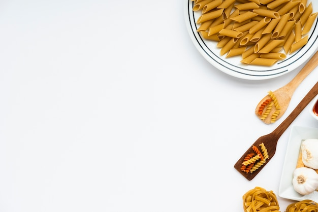 Overhead view of raw italian pasta over white background