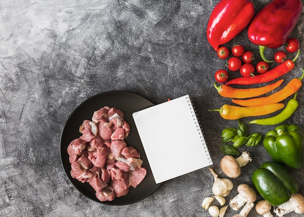 An overhead view of raw meat with notebook and colorful vegetables on stained background