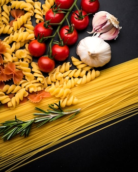 Overhead view of raw pasta; fresh tomato; garlic and rosemary twig on black surface