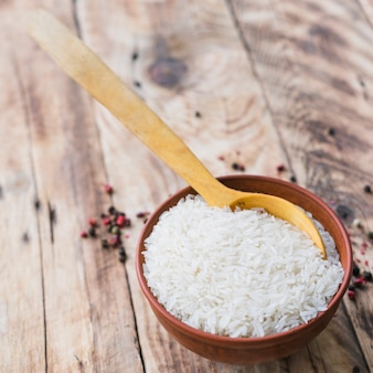 Overhead view of raw white rice bowl with spoon near black pepper spread on wooden table