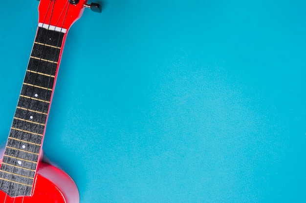 An overhead view of red acoustic classic guitar on blue backdrop