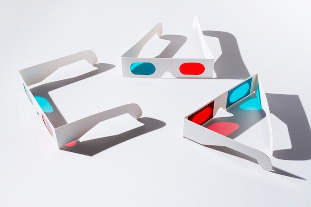 An overhead view of red and blue 3d glasses with shadow on white backdrop