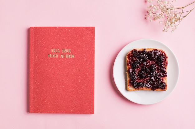 An overhead view of red book; toast with berry jam and baby's breath flowers over pink background