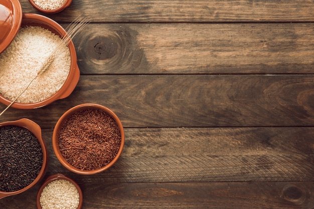 Overhead view of red; brown and white rice bowls on wooden background