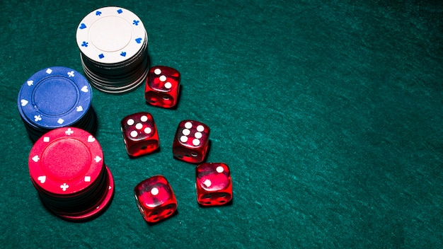 Overhead view of red dices and casino chip stacks on green poker table