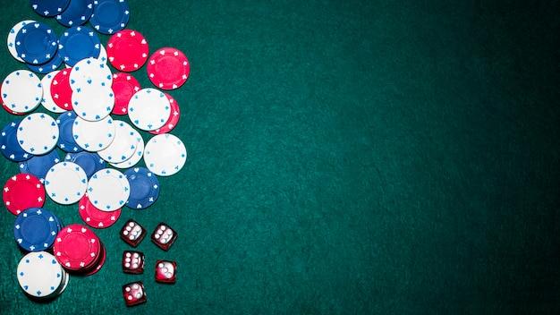 Vista dall'alto di dadi rossi e fiches del casinò su sfondo verde poker