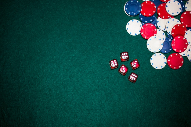 Overhead view of red dices and casino chips on green poker background