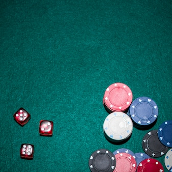 Overhead view of red dices and casino chips stack on green poker table