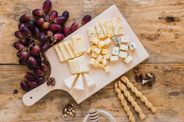 An overhead view of red grapes, variety of cheese, bread sticks on wooden desk