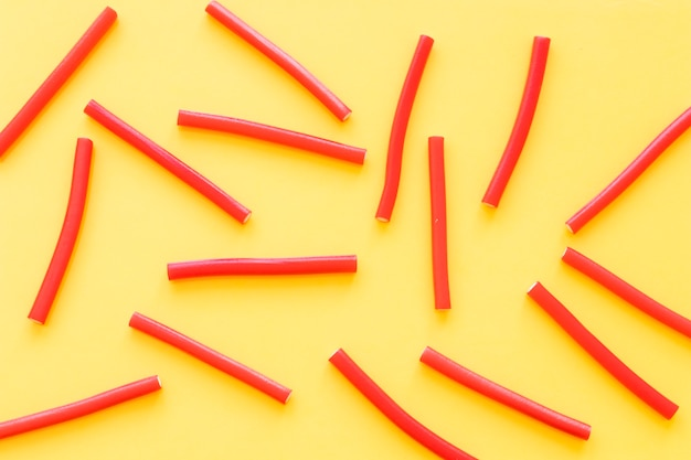 Overhead view of red licorice candies on yellow backdrop