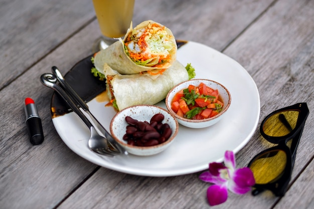 Overhead view of red lipstick, food and purple flower on wooden table. photo of big plate with tasty salad and beans standing beside glass of smoothie.