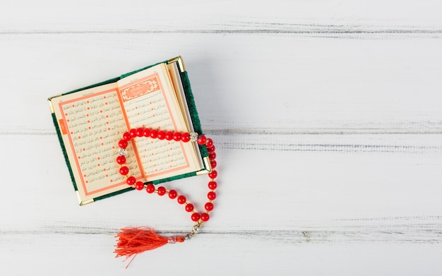 An overhead view of red prayer beads on an open islamic holy book over the white desk