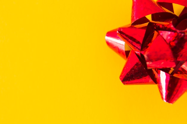 Overhead view of red ribbon bow on yellow background