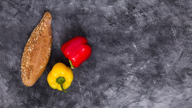 An overhead view of red and yellow bell peppers with loaf of bread against black textured background