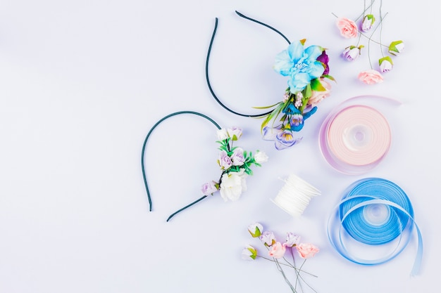 An overhead view of ribbon; artificial flowers; spool for making hairbands on white background