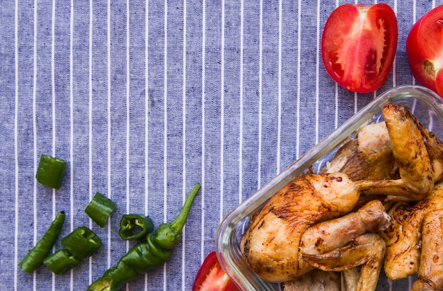 Overhead view of roasted chicken wings with tomato and green chilies against blue table cloth