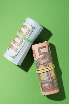 Overhead view of rolled up banknotes on green backdrop