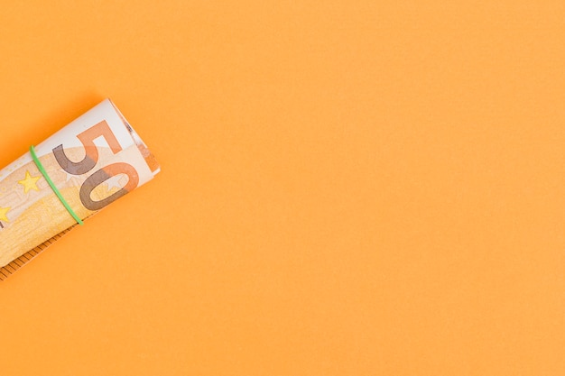 An overhead view of rolled up euro note tied with rubber on an orange backdrop