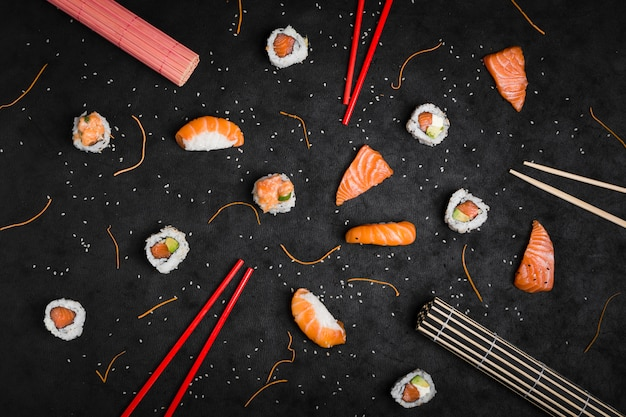 An overhead view of rolled up placemat; chopsticks; sushi; salmon slice; grated carrot; sesame seeds and red chopsticks on black backdrop