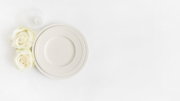 An overhead view of rolled up ribbon; roses and plates on white backdrop