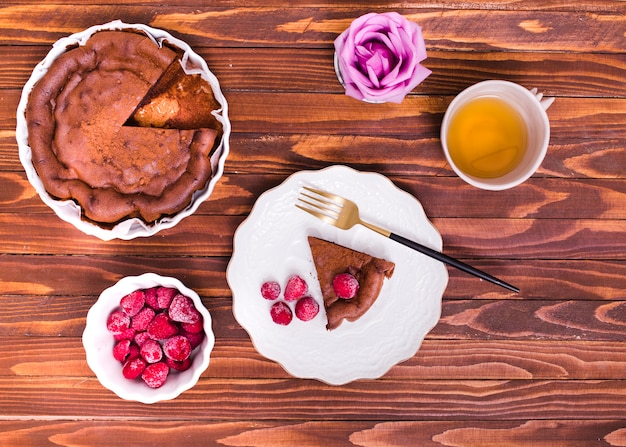 An overhead view of rose; herbal tea; cake slice and raspberry on wooden textured background