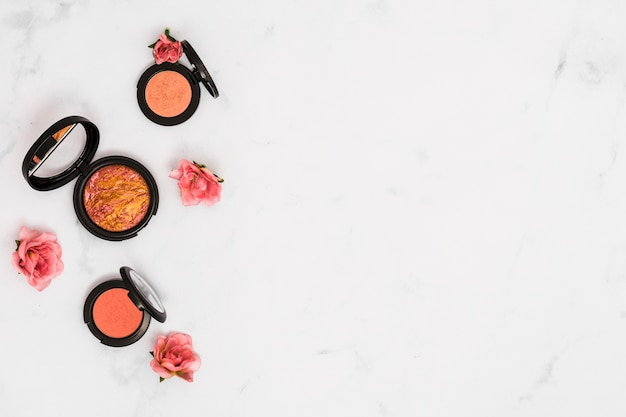 An overhead view of roses with compact face powder on white background