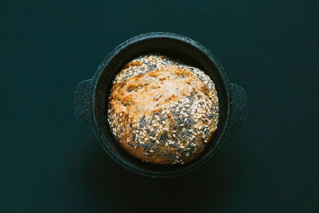 An overhead view of round baked bread in the black background