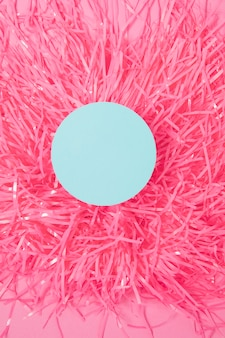 An overhead view of round frame on pom pom against pink background