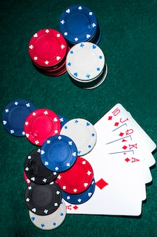 Overhead view of royal flush card and casino chips on poker table