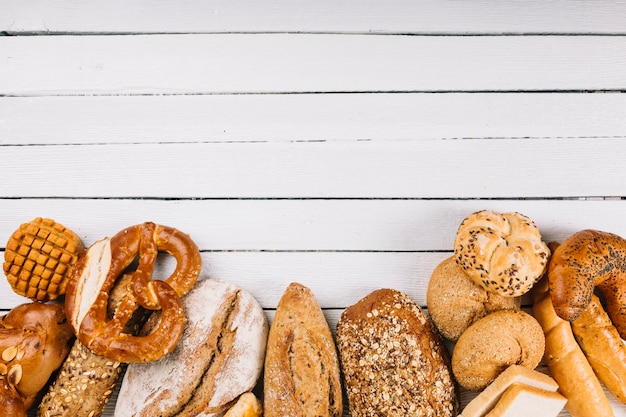 An overhead view of rustic breads on wooden background