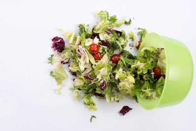 Overhead view of salad fallen from green bowl against white backdrop