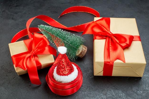 Vista dall'alto del cappello di babbo natale su un rotolo di nastro e bellissimi regali albero di natale su sfondo scuro
