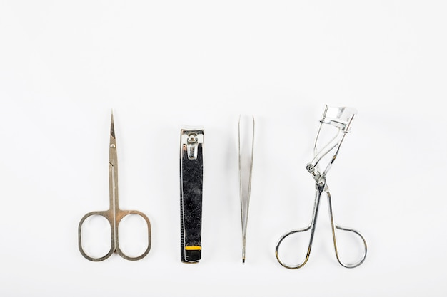 Overhead view of scissors; nail clipper; tweezer and eyelash curler on white background