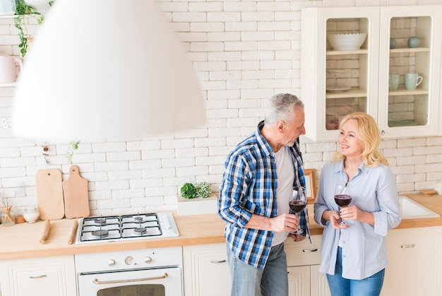 An overhead view of a senior couple holding wineglasses in hand standing in kitchen