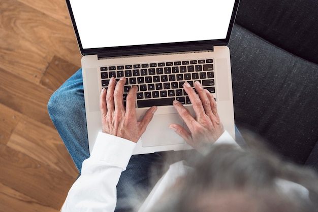 An overhead view of senior man typing on laptop