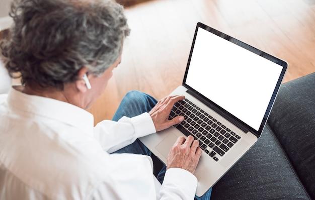 An overhead view of senior man wearing bluetooth earphone using laptop