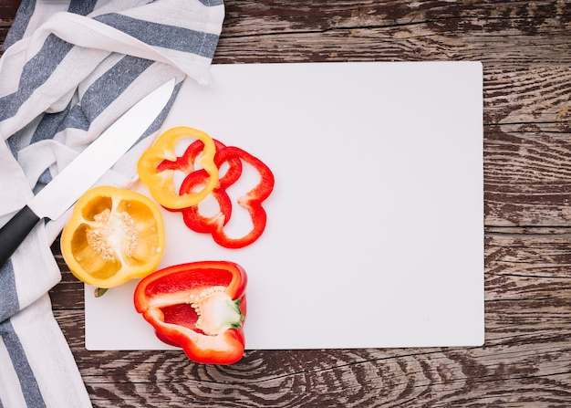 An overhead view of sharp knife and cut slices of bell pepper on white paper over the wooden desk