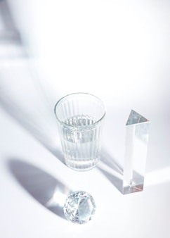 An overhead view of shiny diamond; prism and glass with shadow on white background