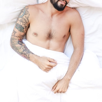 Overhead view of a shirtless man sleeping on bed