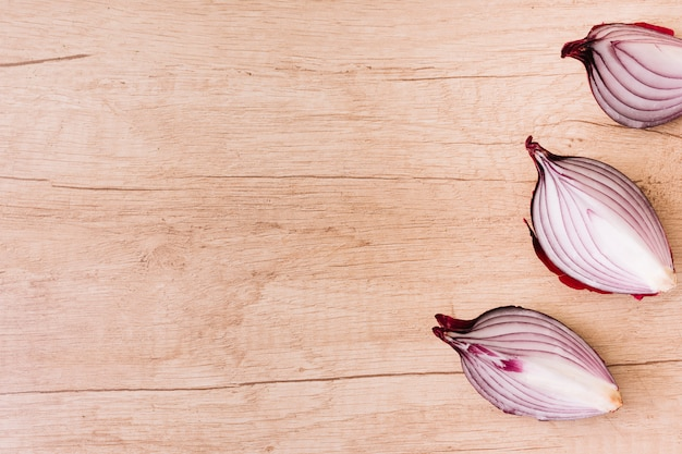 An overhead view of slices of onion on wooden table surface