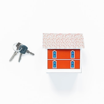 Overhead view of small house model and keys on white surface