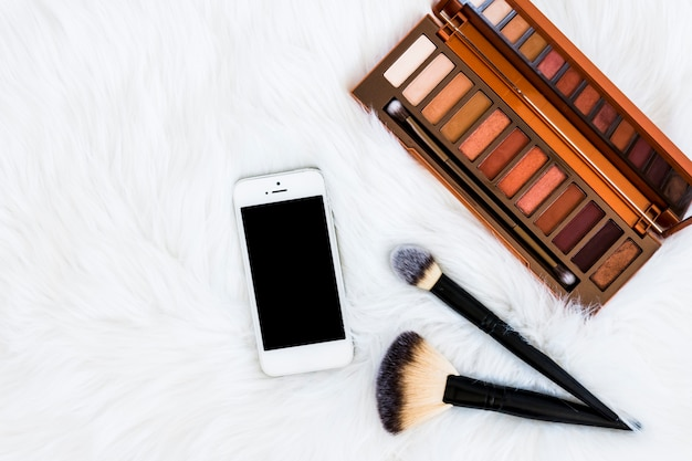 An overhead view of smartphone; makeup brushes and eyeshadow wooden palette on fur backdrop