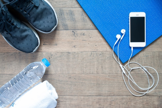 Overhead view of smartphone with earphone on blue yoga mat with black sneaker, bottle of water and towel. fitness and workout concept with copy space