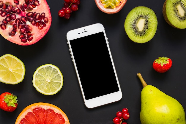 An overhead view of smartphone with many fruits on black background