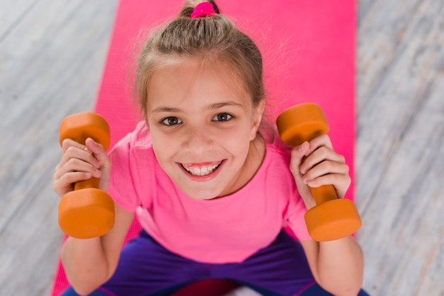 An overhead view of smiling girl holding dumbbell in hands