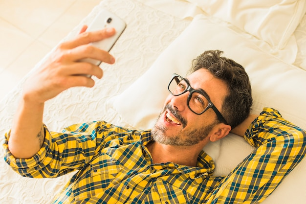 An overhead view of a smiling man lying on bed looking at smartphone