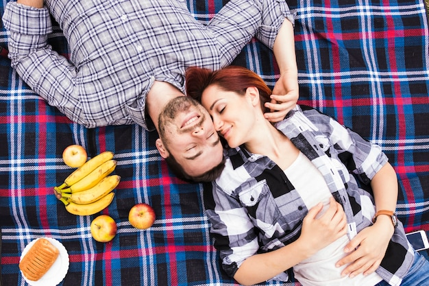An overhead view of smiling romantic young couple lying on blanket with fruits and puff pastry