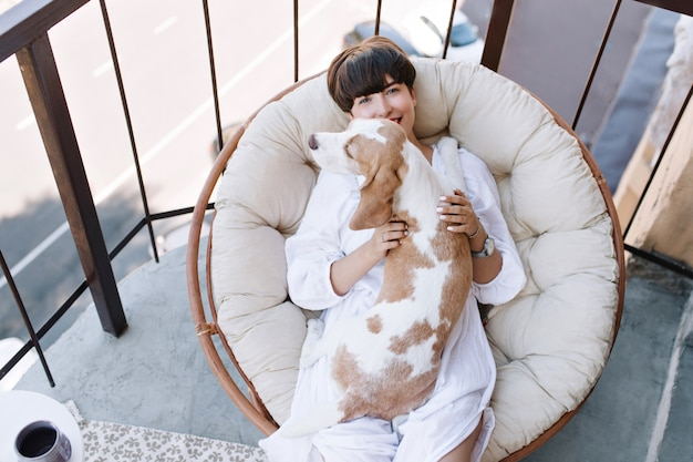 Overhead view of smiling woman in white clothes relaxing in round soft arm-chair with beagle dog
